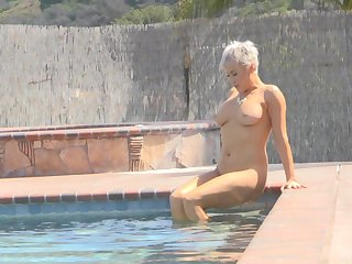 Ryan exposes her huge tits and takes a naked swim in the pool